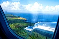 A chrome engine and propellor of a plane flying over tropical islands.