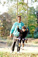 Man pushing son on swing