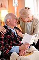 Elderly couple reading card together