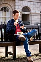A young man sitting on a bench, using his mobile phone