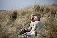 A senior couple sitting amongst the sand dunes, drinking a hot beverage