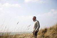 A senior man standing amongst the sand dunes, looking out to sea (thumbnail)