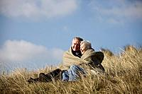 A senior couple sitting amongst the sand dunes, wrapped in a blanket