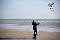 A senior man flying a kite on the beach (thumbnail)