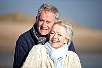 Portrait of a senior couple standing on the beach, embracing