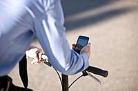 A businessman on his bicycle, looking at a map on his mobile phone (thumbnail)
