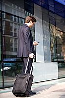 A businessman pulling his suitcase, using his mobile phone