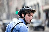 A businessman wearing a cycling helmet, commuting to work