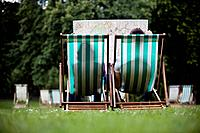 A young couple sitting on deckchairs in St James Park, looking at a map