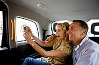 A middle_aged couple in a London taxi, taking a photograph