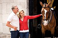 A middle_aged couple standing at Horse Guards, woman stroking a horse