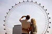 A middle_aged couple photographing the London Eye, rear view