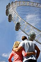A middle_aged couple standing near London Eye, arm in arm