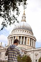 A mid_adult man standing in front of St Paul's cathedral, looking at a map
