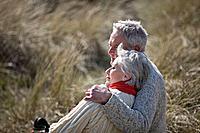 A senior couple sitting amongst the sand dunes, embracing