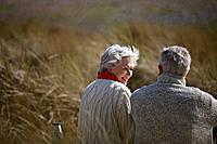 A senior couple sitting amongst the sand dunes, talking