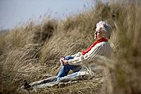 A senior woman sitting amongst the sand dunes, enjoying the sun