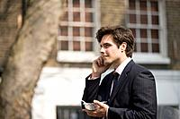A businessman talking on his mobile phone, eating take_away food