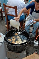 Woman cooking Spanish bunuelos at Balearic Culture day in Santa Eulalia, Ibiza, Spain