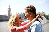 A middle_aged couple standing near the Houses of Parliament, embracing