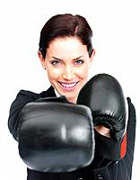 Portrait of a happy young female entrepreneur wearing boxing gloves against white background