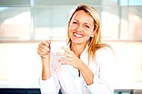 Portrait of a smiling young casual businesswoman driking coffee