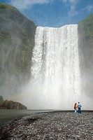 two visitors at the riverside of the Skoga in front of the impressive waterfall Skogafoss, Iceland, Skogar