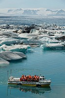 excursion boat on glacial lake Joekulsarlon full of melting ice in front of glacier Breidamerkurjoekull, Iceland
