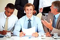 Happy young businessman sitting with his colleagues at a meeting in office