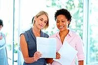 Two business women holding documents at office