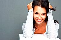 Pretty woman smiling while leaning on shelf with hands on her head