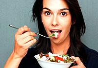 Pretty woman eating bowl of salad