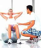 Woman sitting on exercise ball assisted by personal trainer