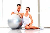Portrait of smiling young woman and trainer with fitness ball