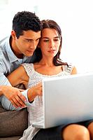 Young man and woman working on laptop at home