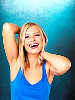 Portrait of cheerful woman smiling on blue background