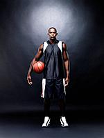 Portrait of a young male basketball player standing with basketball against black background