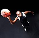 Top view of a healthy young male basketball player practicing a hoop shot against black background