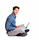 Executive sitting on the floor cross_legged with laptop