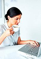 Portrait of a smart young business woman having a cup of coffee while using laptop in the office