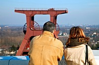 couple on the new viewing platform looking at the head gear of coal mine Zollverein Schacht XII, Germany, North Rhine_Westphalia, Ruhr Area, Essen