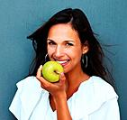 Head shot of woman holding apple against blue background