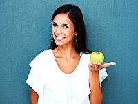 Smiling woman holding apple in palm of hand