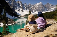 Brother and sister admiring the view from the rockpile viewpoint at Moraine Lake near Lake Louise, Banff National Park, Alberta, Canada.