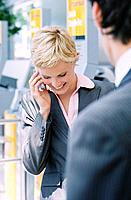 Businessman and Businesswoman Using Cell Phone