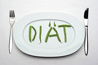 place setting with only some green beans on the table forming the word ´DIAeT´ ´diet´