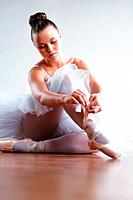 Portrait of a young and beautiful Ballerina putting on her ballet shoes