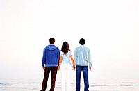 Three Young People Standing by the Sea