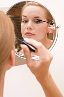 young pretty woman doing makeup, using mascara