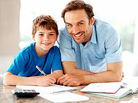 Portrait of a smiling young father helping to his son doing homework _ Indoor